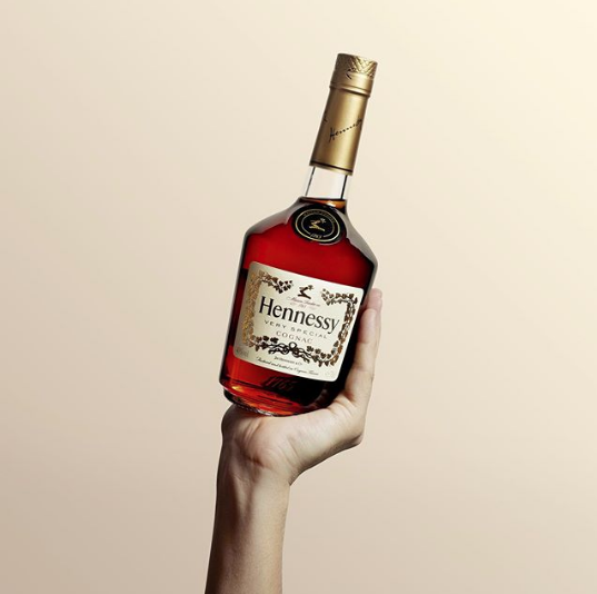 Hand holding up bottle of hennessy