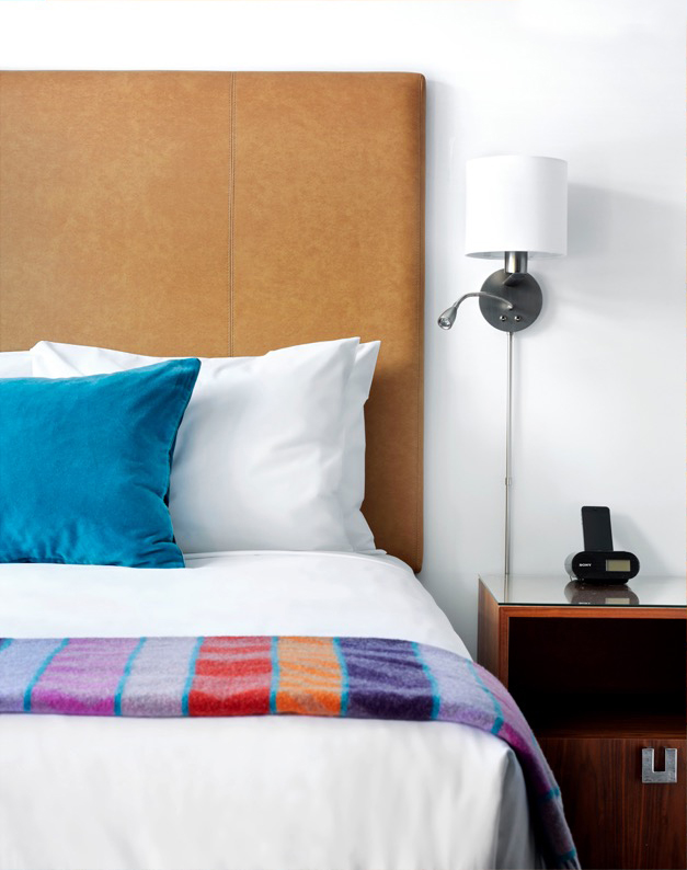 Motel room with white linens and colourful blanket