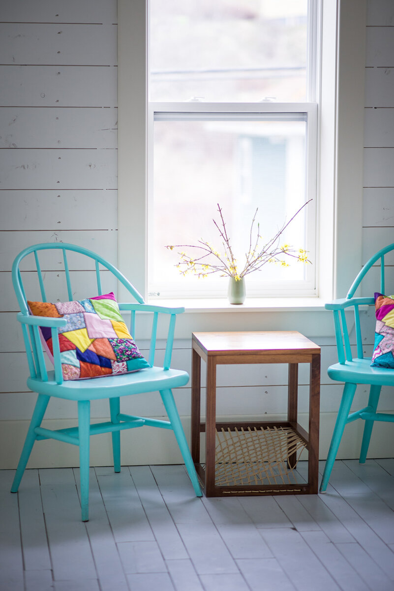 Motel room with blue chairs and quilted pillow