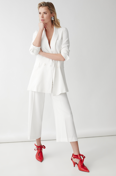 Meghan Chayka standing in white suit with red shoes