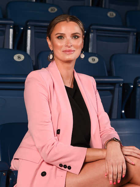 Meghan Chayka sitting in pink suit with black shit and blue stadium seating