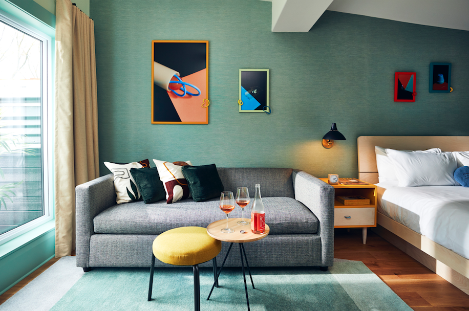 Colourful motel room with couch and wine on table