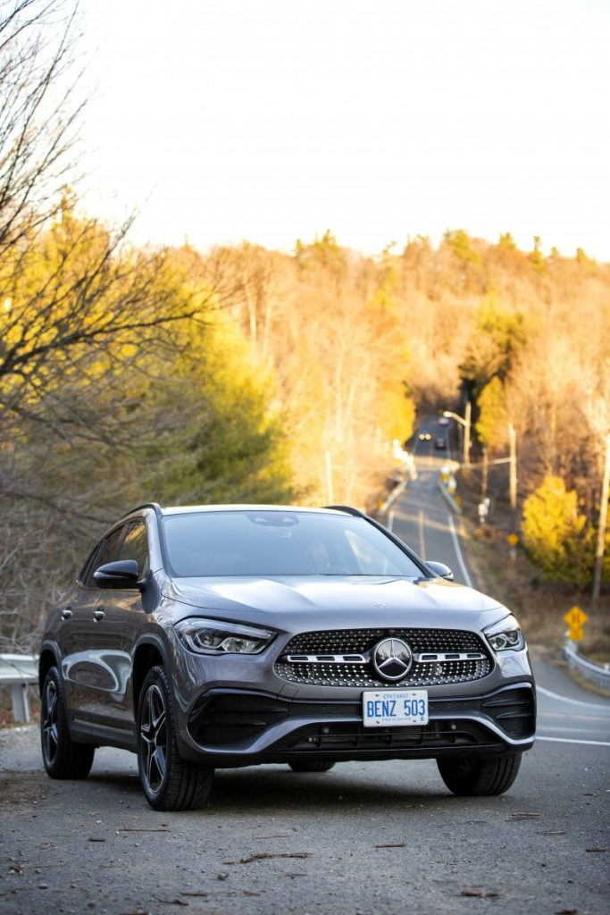 Mercedes Benz GLA parked on road with forest backdrop