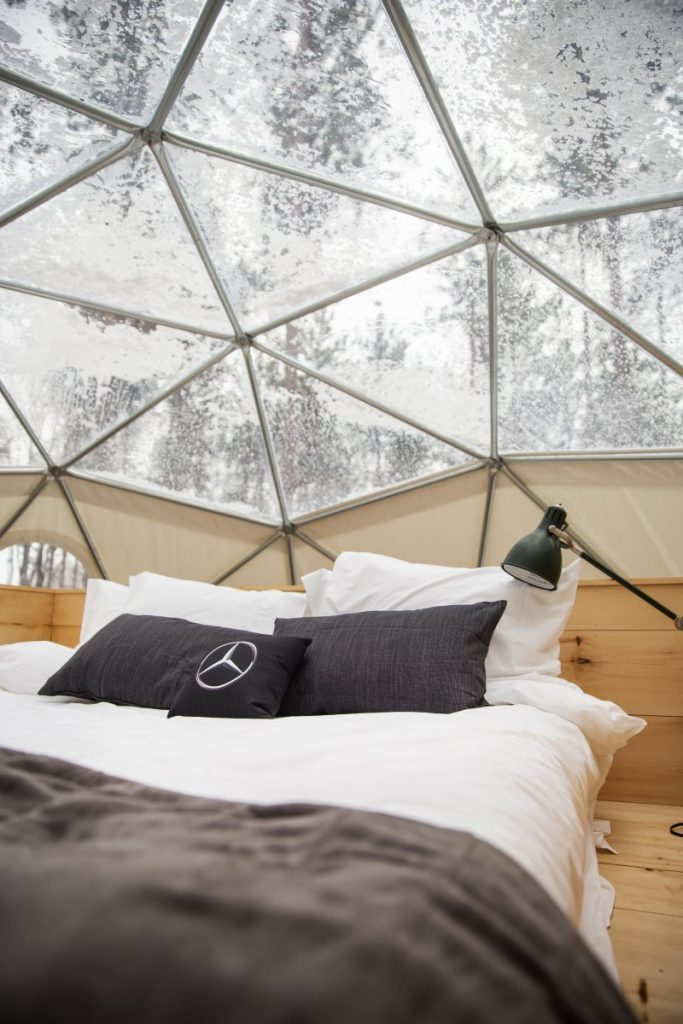 Inside geodesic glamping dome with Mercedes Benz branded pillow on bed