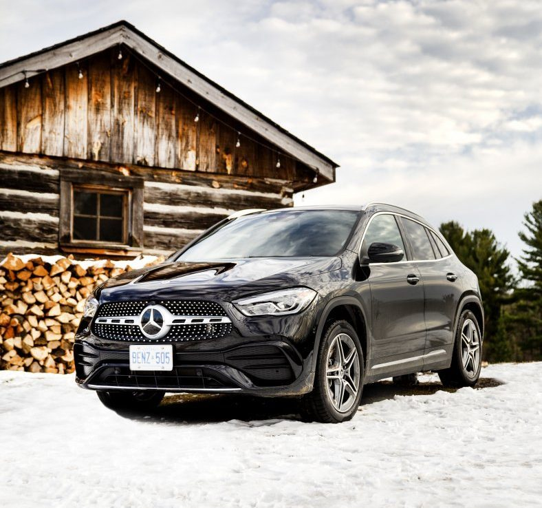 Mercedes Benz GLA parked on snow against wood cabin