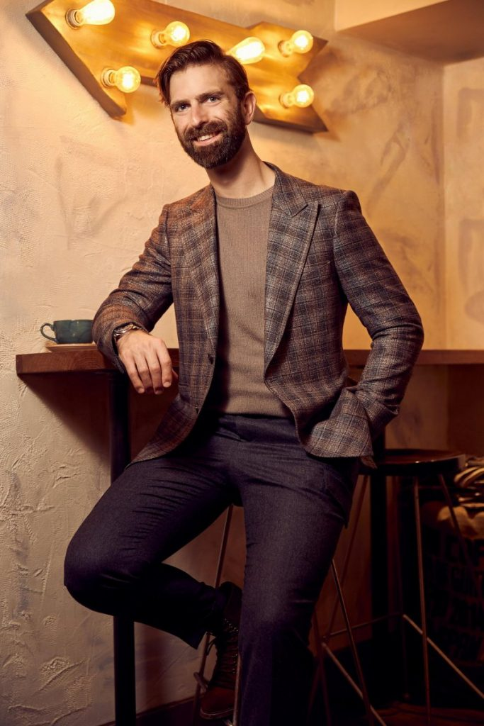 Ian Rosen in sports jacket, sweater and pants leaning against coffee table