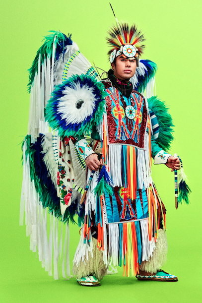 Notorious Cree in traditional Indigenous regalia against green background