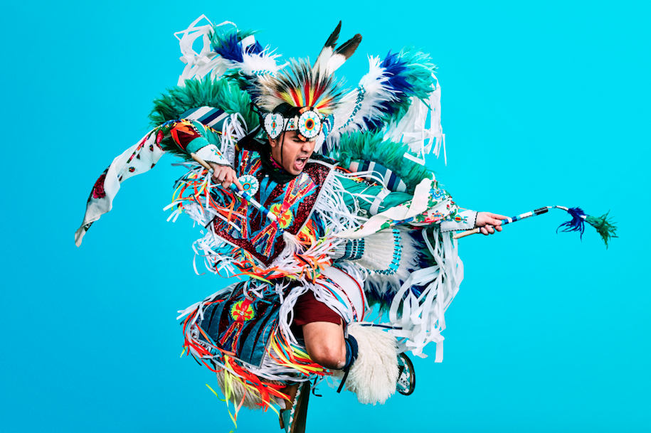 Notorious Cree in traditional Indigenous regalia jumping up against blue background