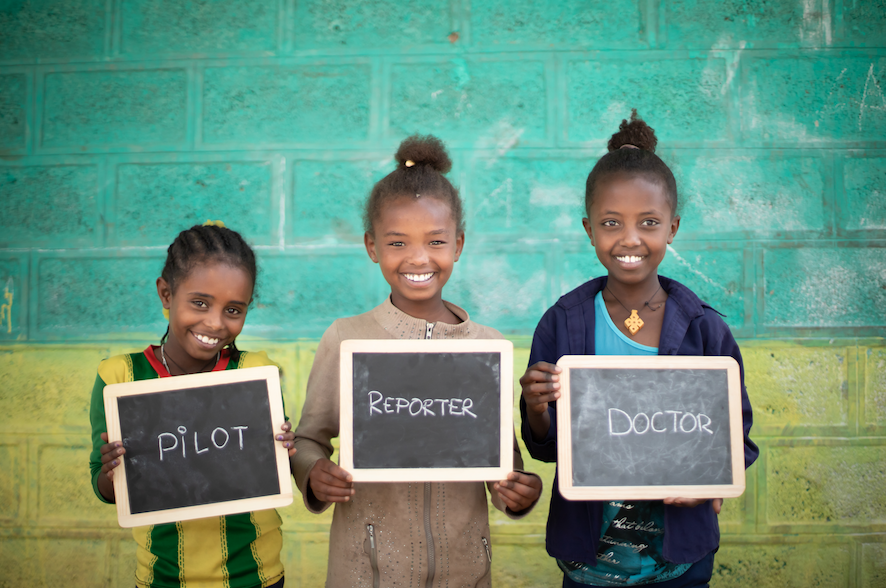 Children holding up small chalkboards with words pilot, reporter, and doctor written on them