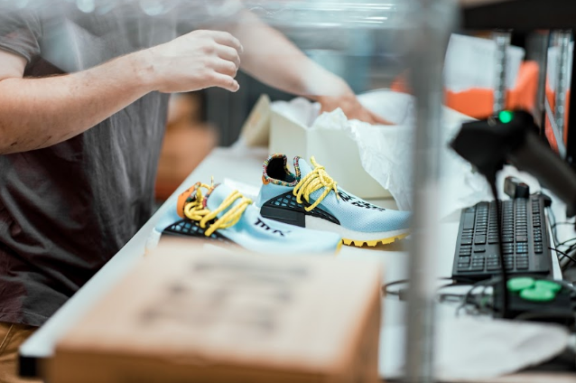 StockX Data Processing centre with Nike sneakers on table and person handling it