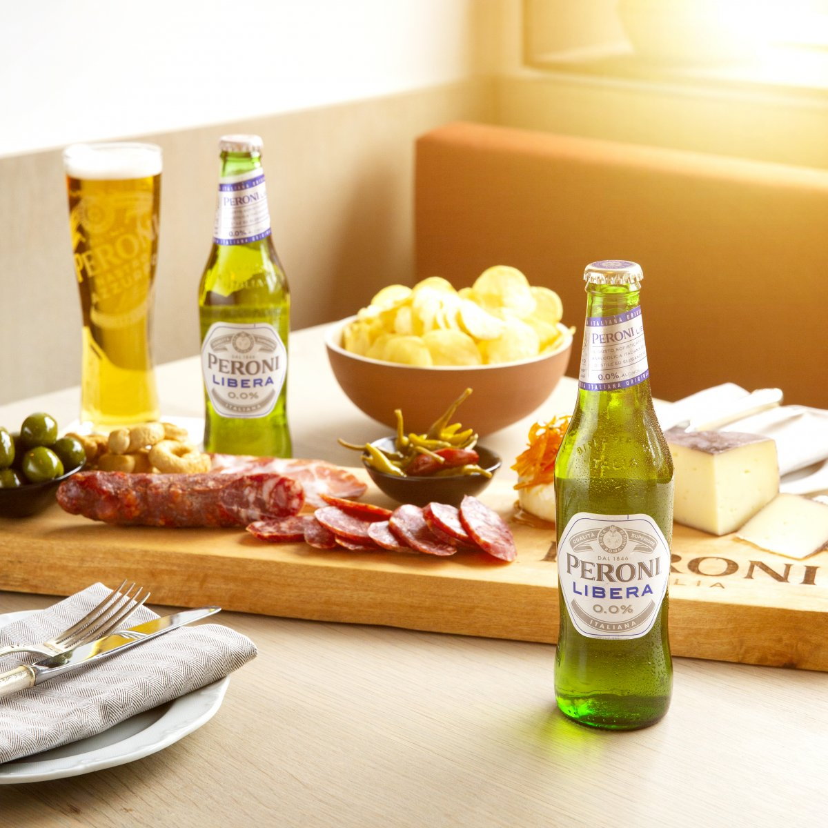 Board of assorted meats and cheeses accompanied by Peroni Libera a new non-alcoholic beer.