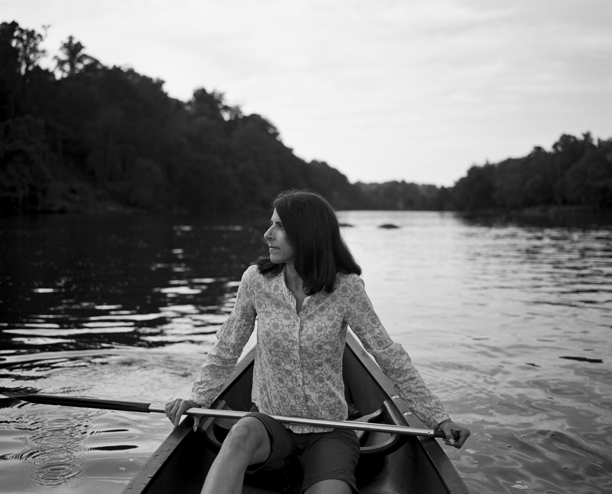 A black and white photo of a woman, Florence Williams, an Arc'tyrex ambassador, sitting in a canoe on the water, looking to her right.