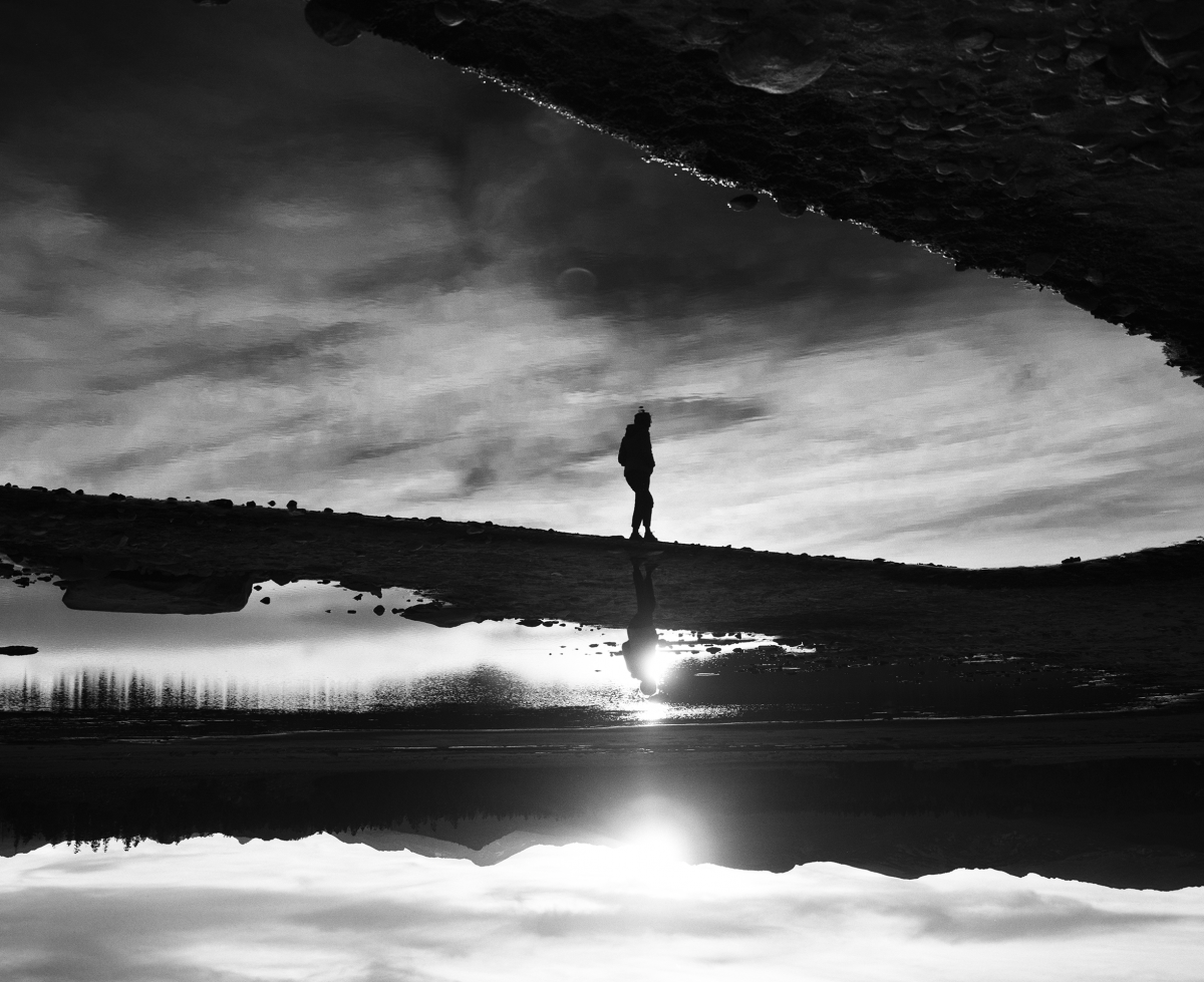 Black and white image for Arc'tyrex of a person walking on a bridge over a body of water.