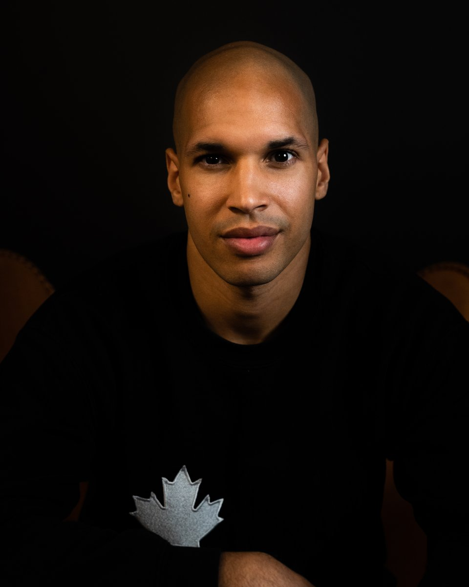 Portrait of a Black man, wearing a black long sleeve shirt, with a white Maple leaf on the top left hand corner of the shirt. His name is Marc Lafleur, CEO and co-founder of truLOCAL
