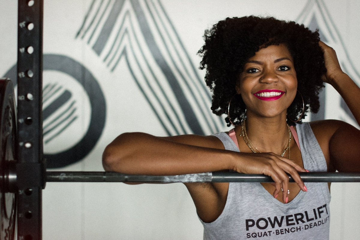 A Black woman smiles at the camera while standing at a squat rack. The woman is Chrissy King.