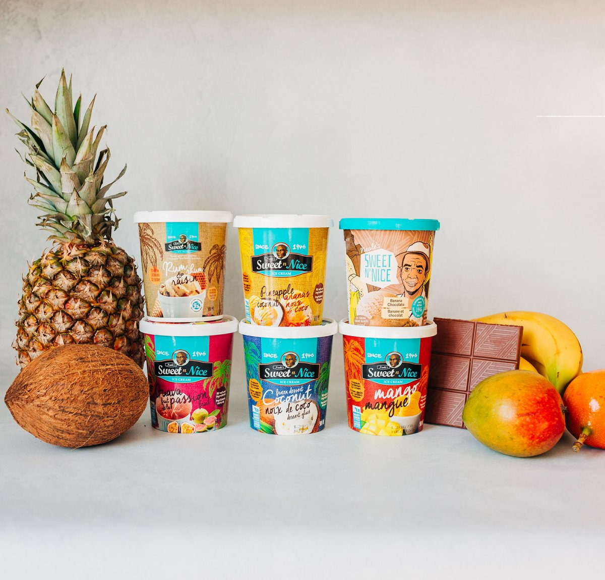 Six Neale's Sweet N' nice ice cream cartons surrounded by a pineapple, a coconut, chocolate, and mangos
