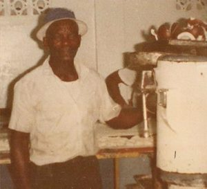Old film photo of Charles Neale, a black man wearing a white button up shit and a blue brimmed hat, standing next to an ice cream machine.