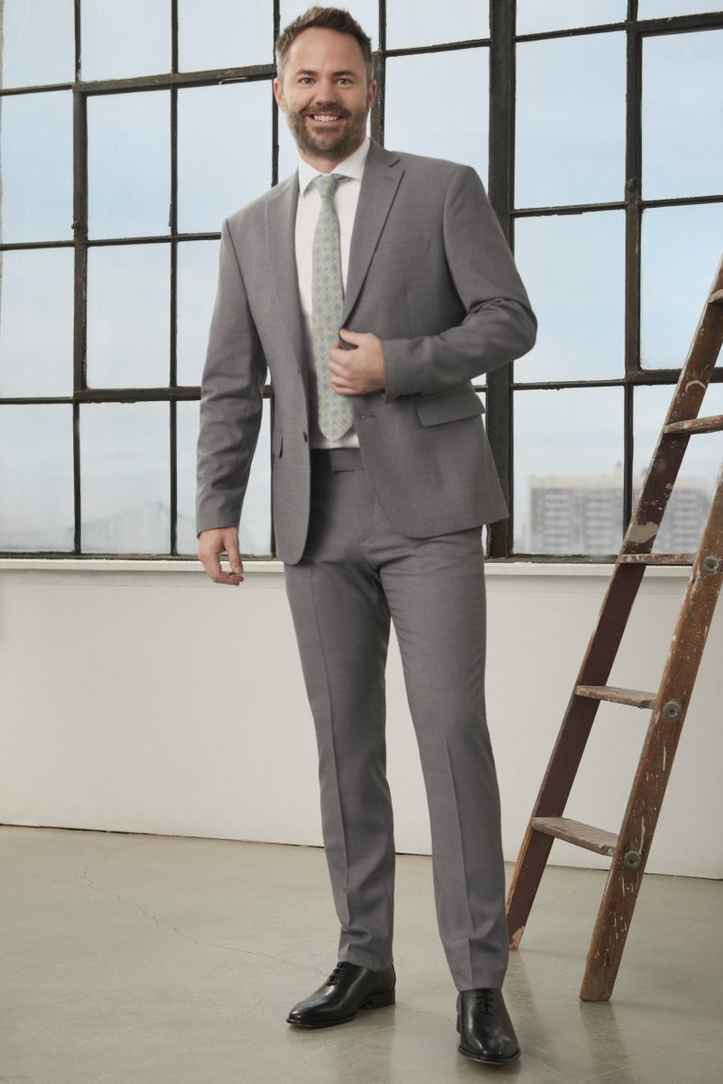 A white man, Lane Merrifield, posed standing in a grey suit.