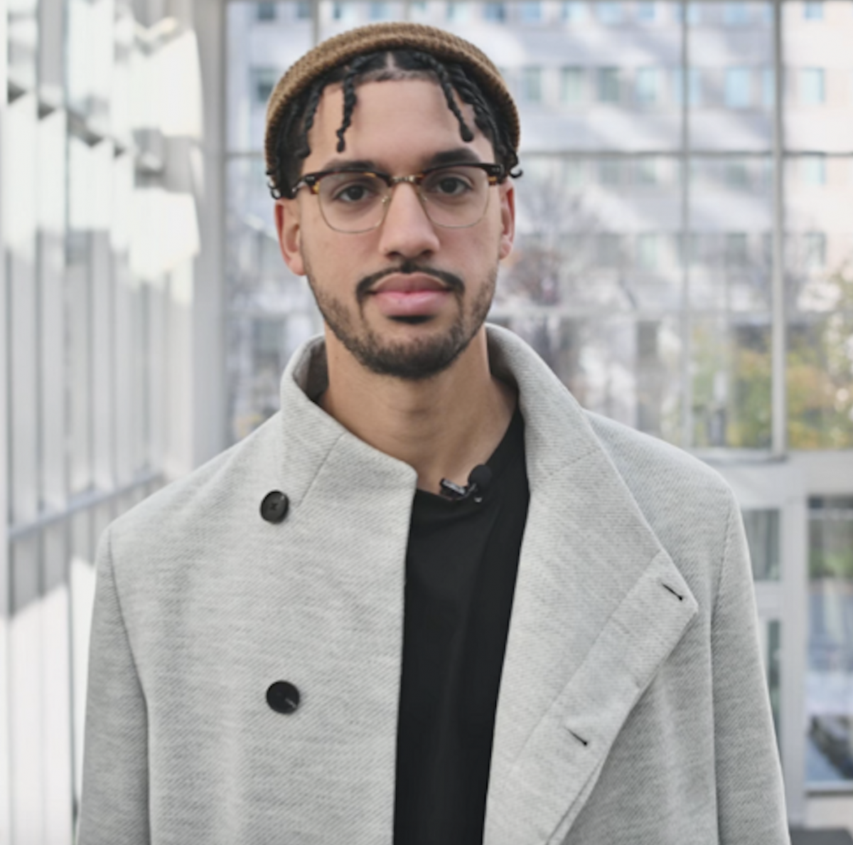 A Black man with a beanie hat and glasses, wearing a grey plaid coat stares at the camera. He is Phil G. Joseph, creator of Rep Matters.