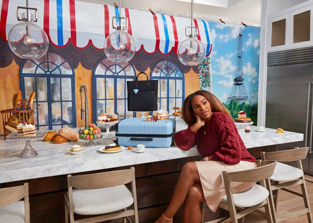 Serena Williams sitting at bar counter with blue Away luggage and confections