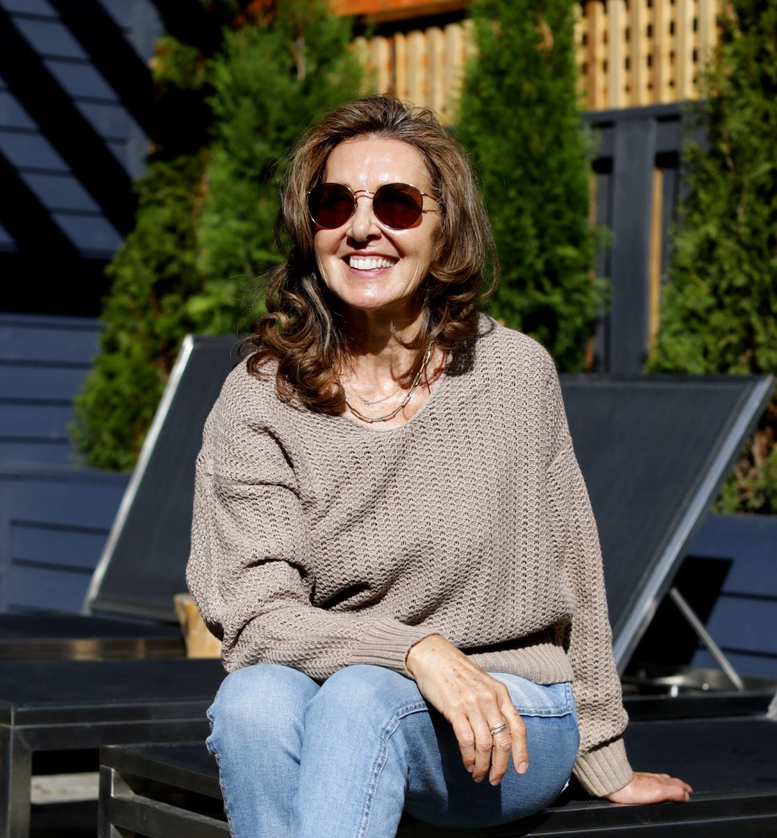 Pivot Skincare founder Cindy Berg sits on a lawn chair and smiles in the sun.