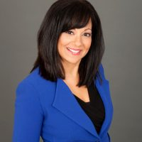 Headshot of a brunette woman wearing a blue blazer. She is the author of the op-ed about women's financial literacy.