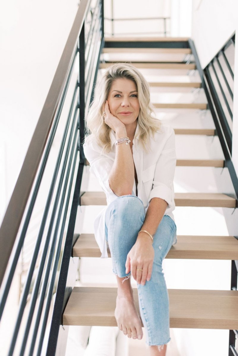 A blonde woman, Janey Reilly, founder of WeeSleep, wearing blue weans and a white shirt sits on wooden stairs. She smiles at the camera.