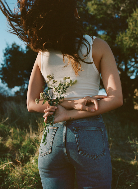 Woman in jeans holding flowers