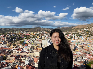 An asian woman, co-founder of Deel, Shuo Wang, stands in front of a city landscape.