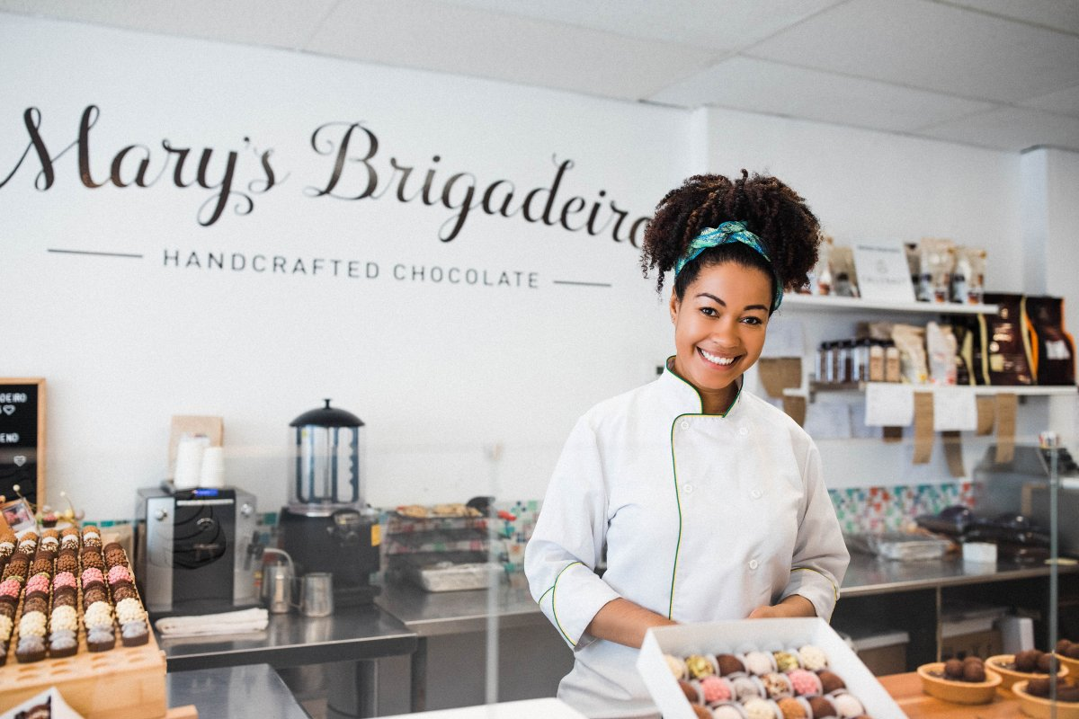 Woman in a white chef's jacket holds a tray of small round chocolates in a kitchen, to represent how the Black Entrepreneur Startup Program wants to help young Black entrepreneurs succeed.