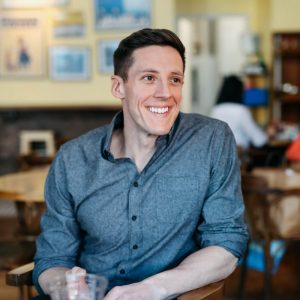 A man wearing a button up shirt sits at a table and smiles. His name is Sean Hurley, he is the writer of this article talking about the success of a startup.