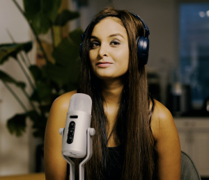 A photo of Fatima Zaidi in front of a podcast microphone smiling at the camera to showcase her as the author of this article about philanthropic podcasts