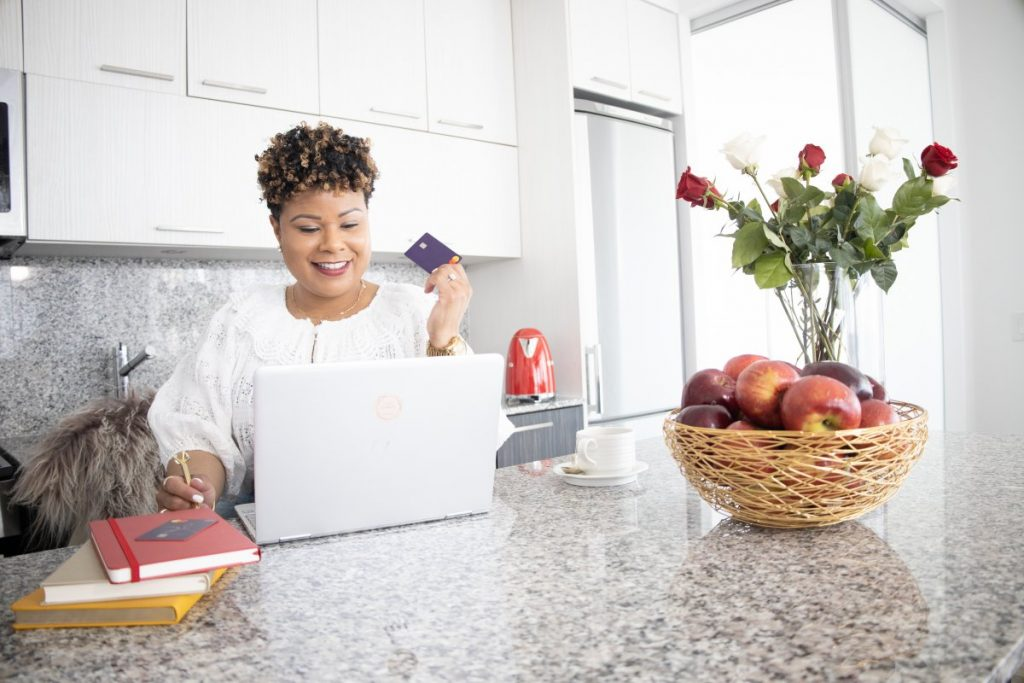 Vanessa Bowen, Creator of Mint Worthy at her Kitcen counter with her laptop, holding up a credit card. Her countertop has a vase of flowers and a fruit basket on it.