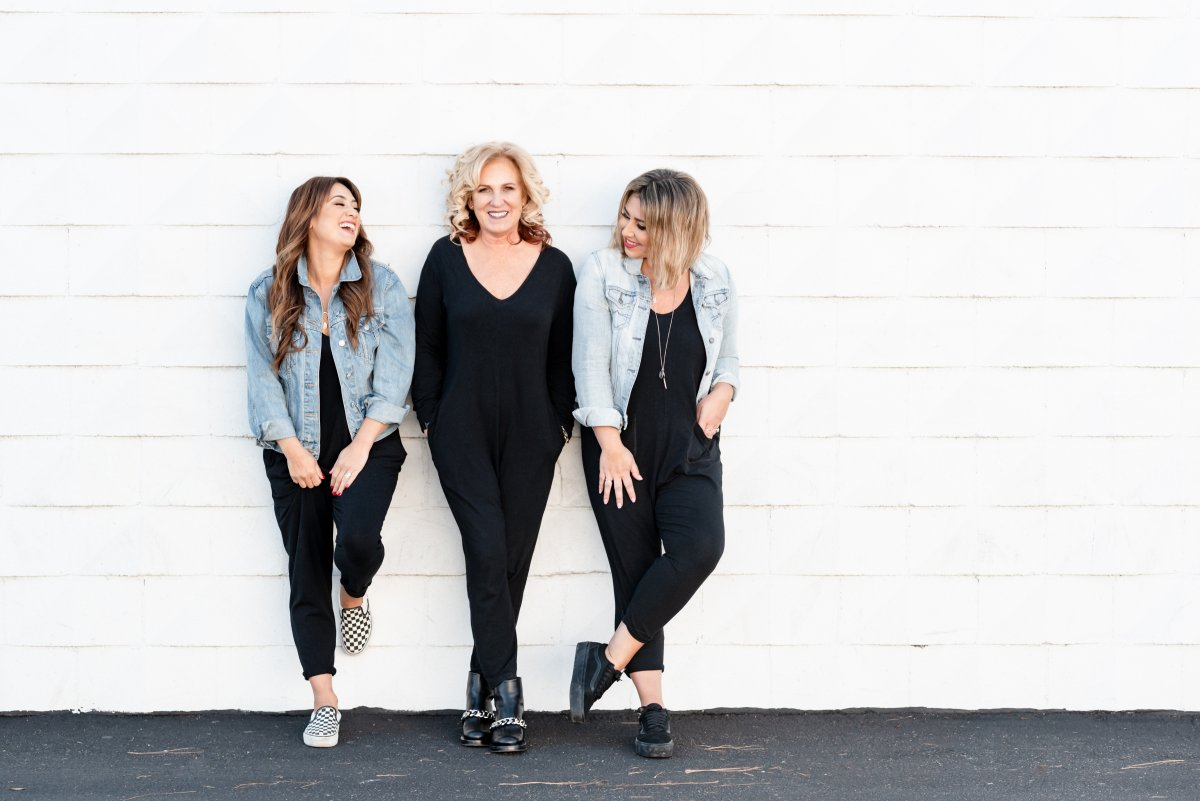 Mercedes LaPorte(L), Teresa Freeborn(C), and Ashley Freeborn(R) of Smash + Tess stand together laughing and smiling against a wall outside.