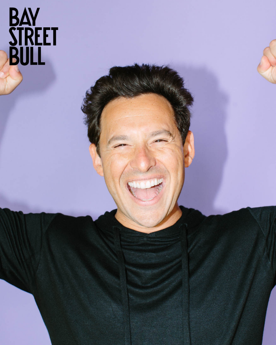 Shopify president Harley Finkelstein with arms up against purple background