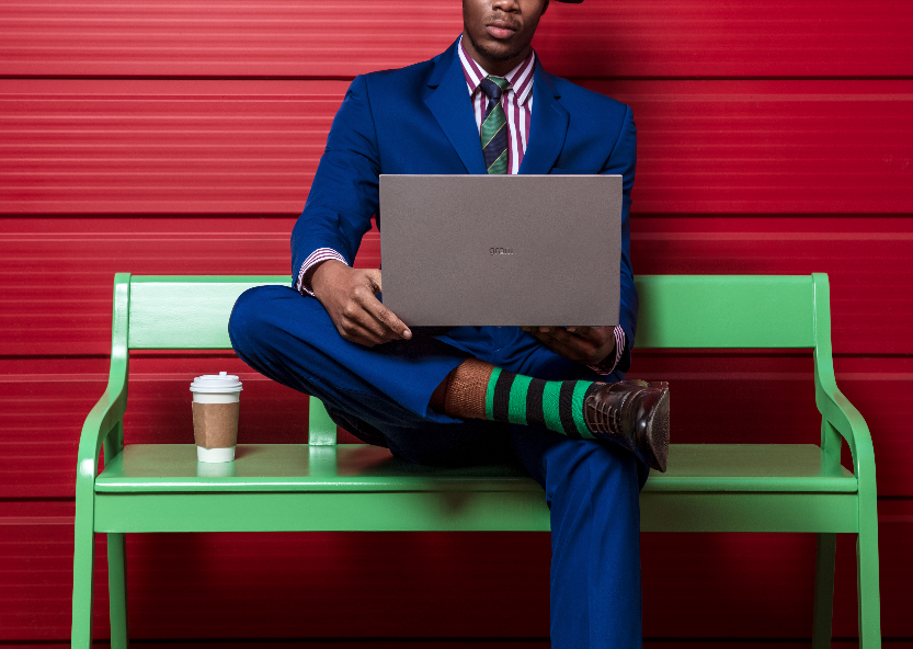 Man in blue suit sitting on bench with laptop