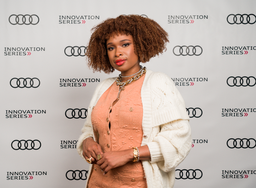 Jennifer Hudson in white cardigan and peach blouse against Audi Innovation Backdrop